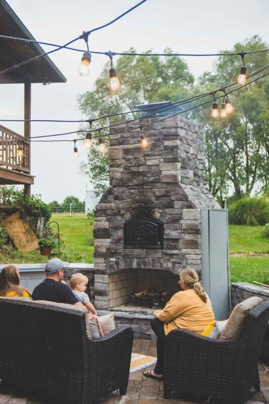 People sitting on chairs in front of a brick oven