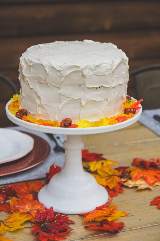 White cake with fall colored jewels on a white cake stand