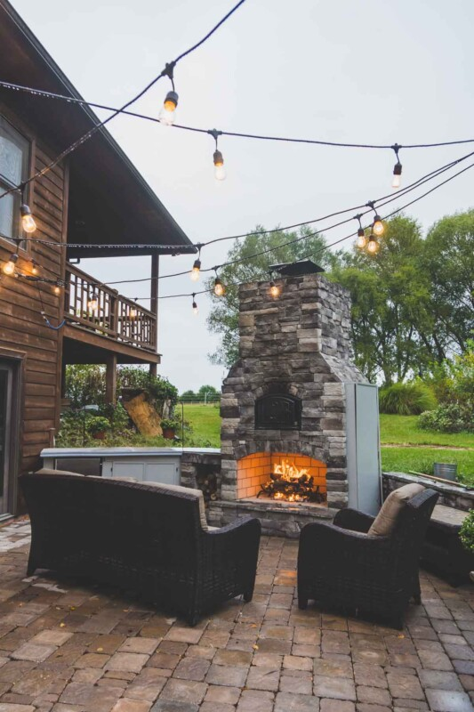 Outdoor entertaining space with a fire in the fireplace