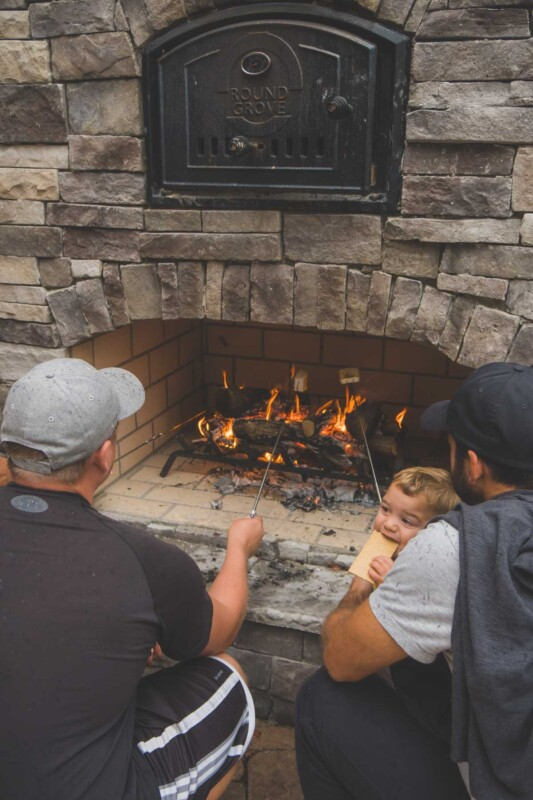 Two men and babies making s'mores in a fireplace