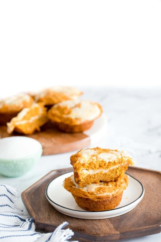 Two pumpkin cream cheese muffins on a white plate on a wood board with muffins in the background