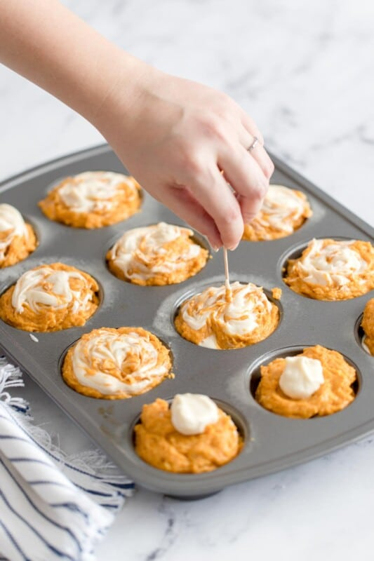 A hand with a toothpick over a muffin tin full of pumpkin cream cheese muffin batter