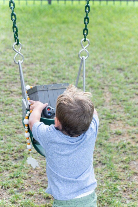 Baby getting a treasure box out of a swing