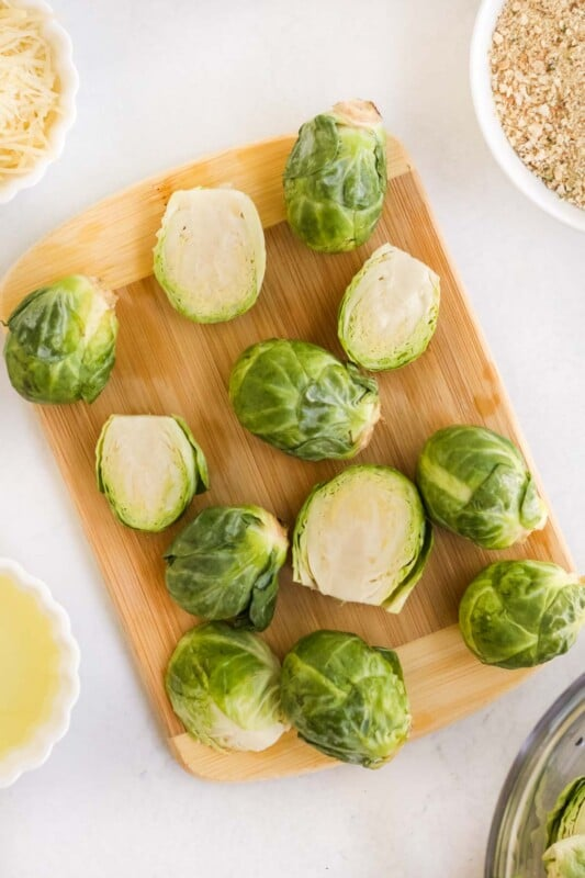 Brussels sprouts cut in half on a cutting board