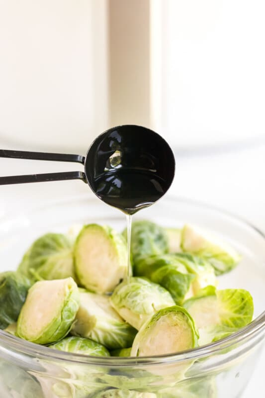 Measuring spoon pouring olive oil on a bowl of brussels sprouts