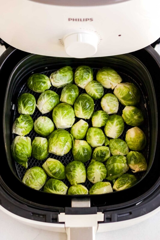 Uncooked brussels sprouts in an air fryer drawer