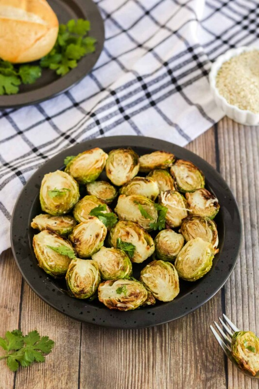 Dark plate with air fryer brussel sprouts on it with a napkin in the bakground