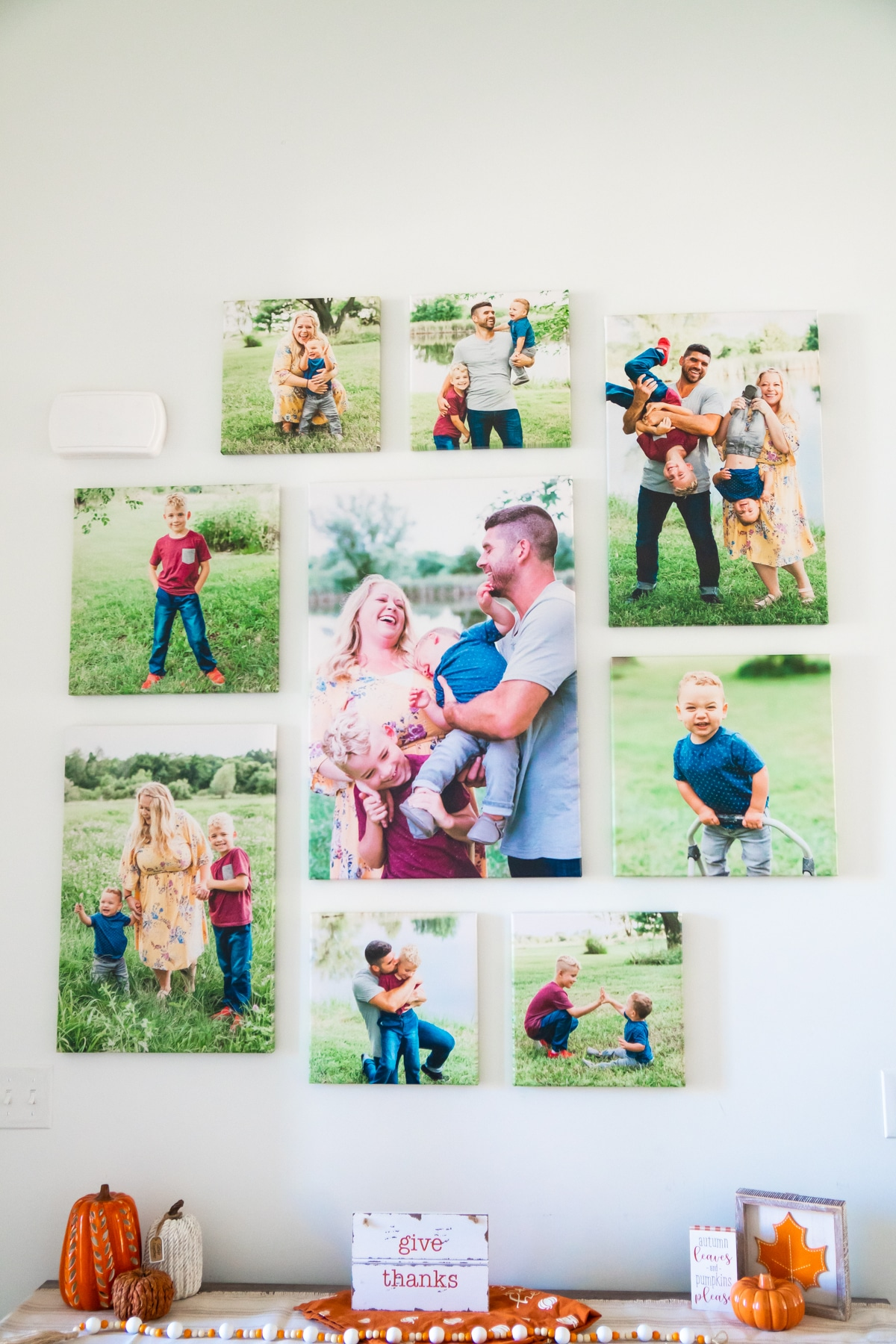 DIY photo wall made with canvases above an entry table