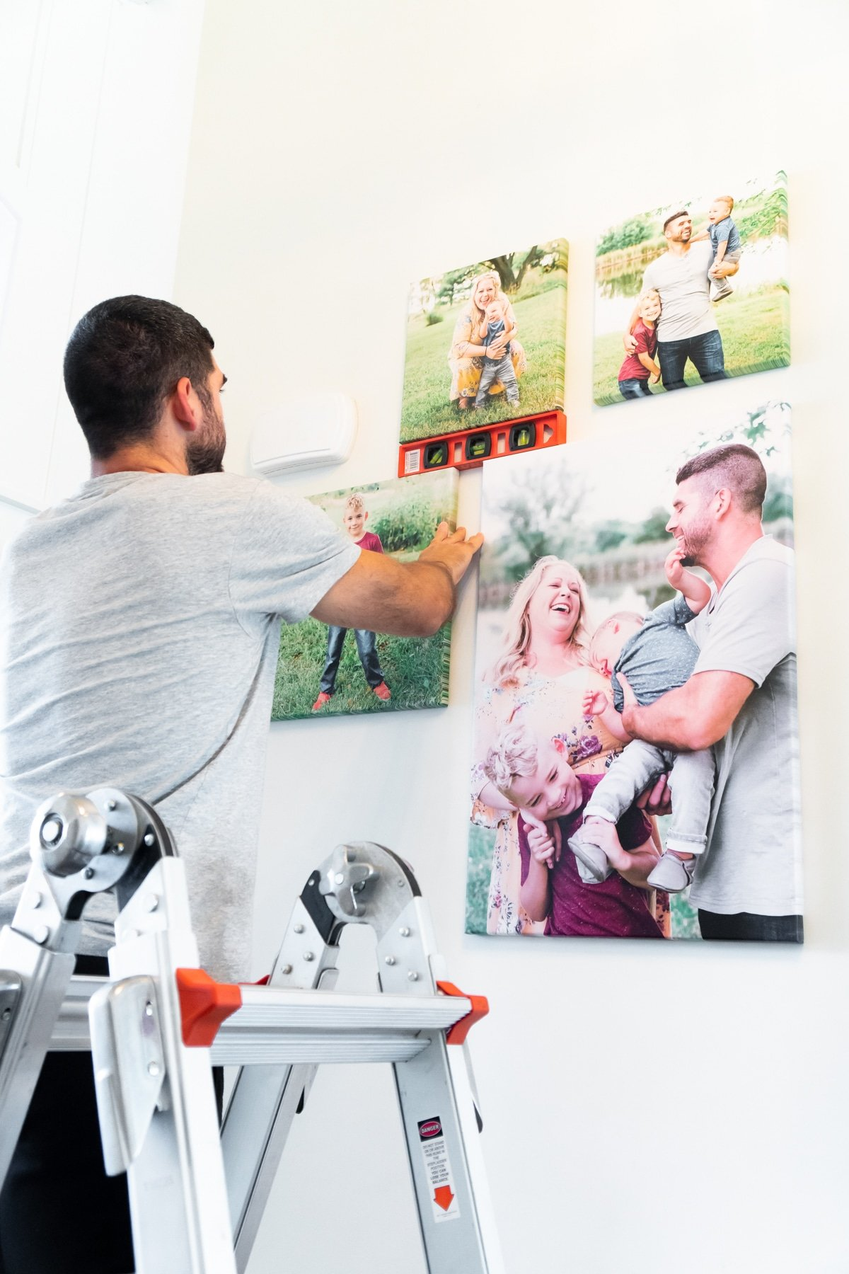 Man on a ladder adding canvases to a DIY photo wall