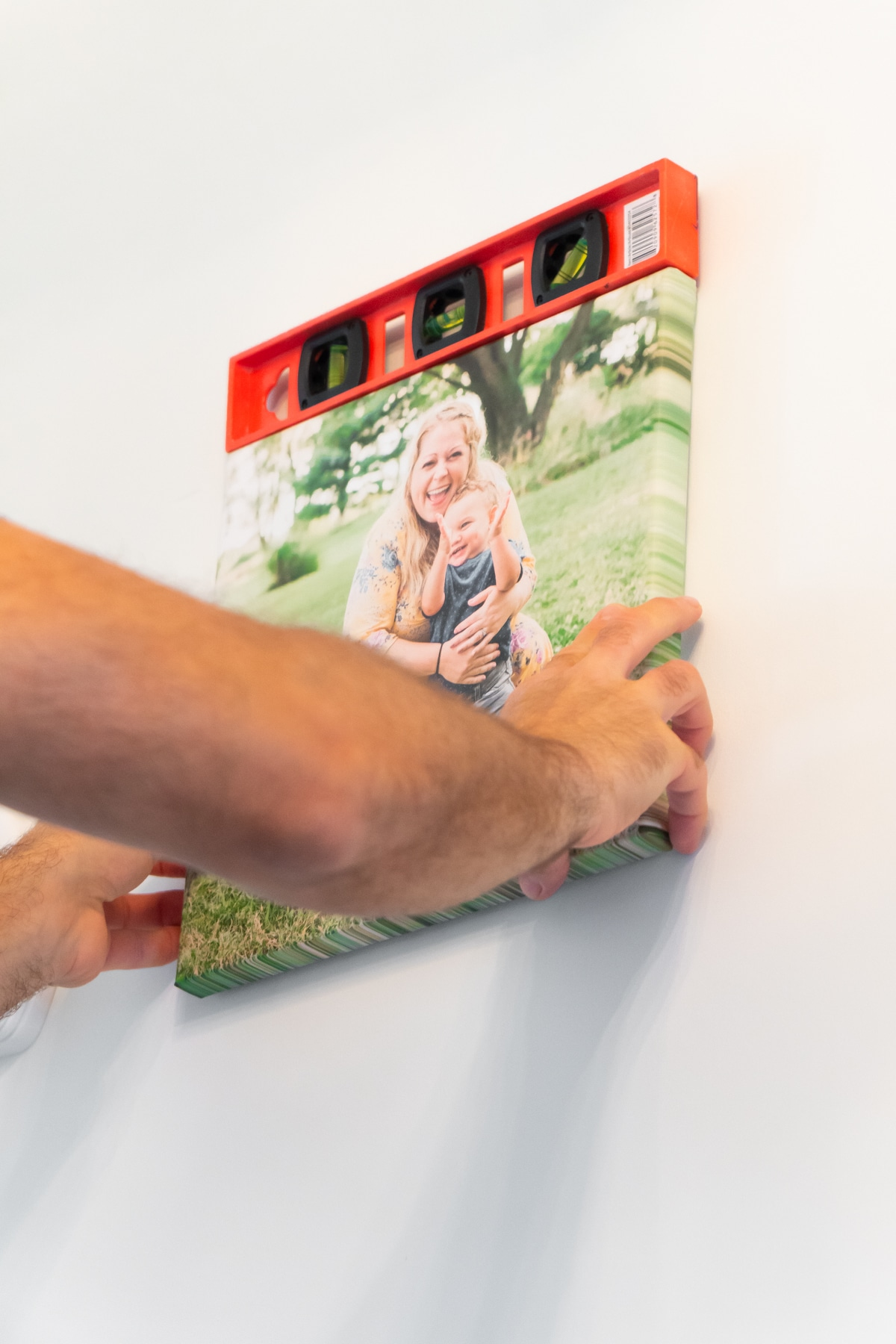 Man's hands holding a canvas on a wall with a level on top