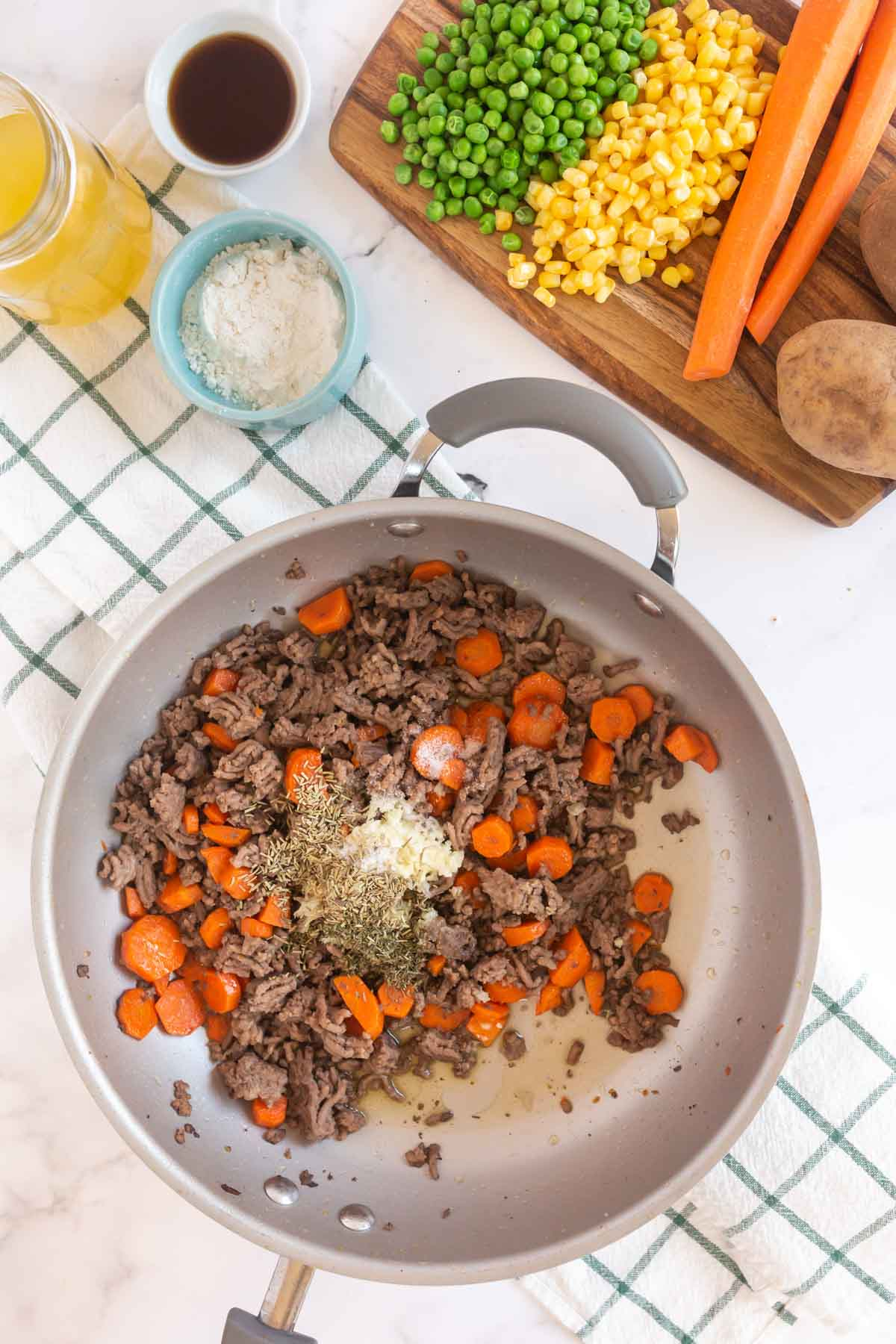 Spices, ground beef, and carrot in a metal pan