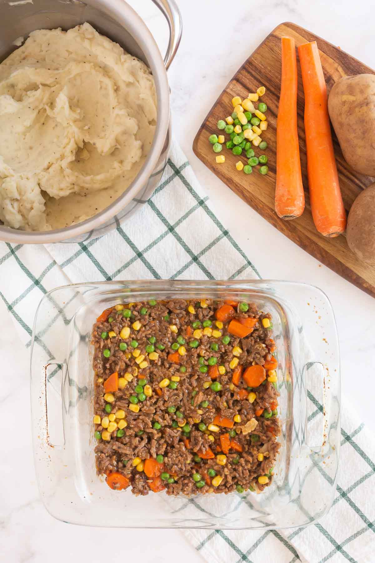 Sheperds pie filling in a square glass baking dish
