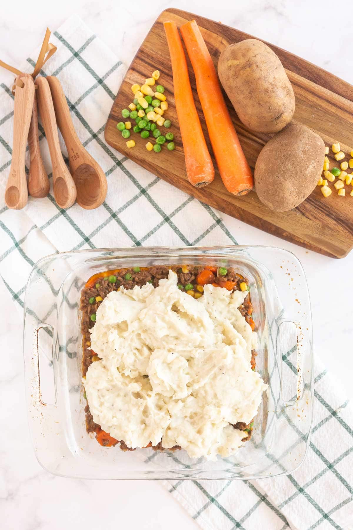 Mashed potatoes on top of shepherd's pie filling in a glass baking dish