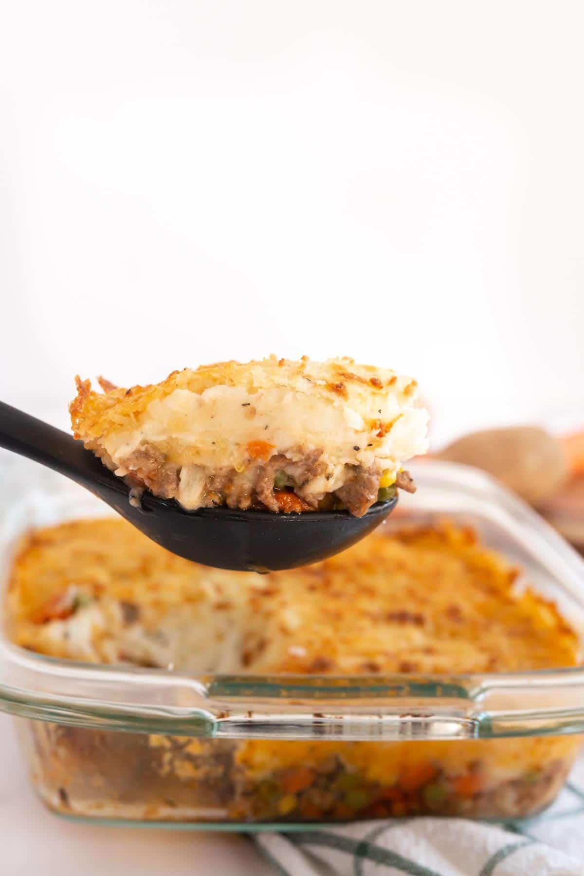 Spoon full of shepherd's pie in front of a pan of shepherd's pie