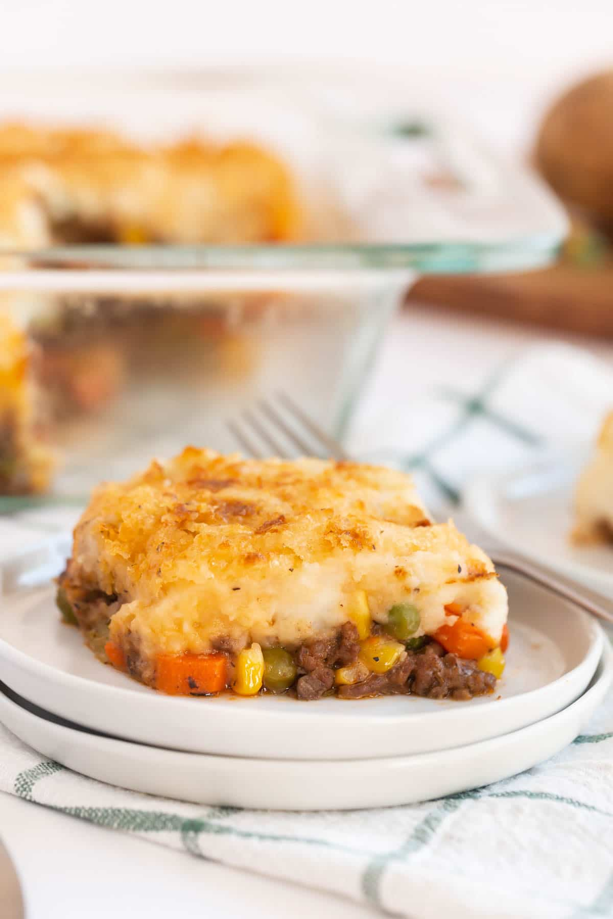 A white plate with a piece of easy shepherds pie on it