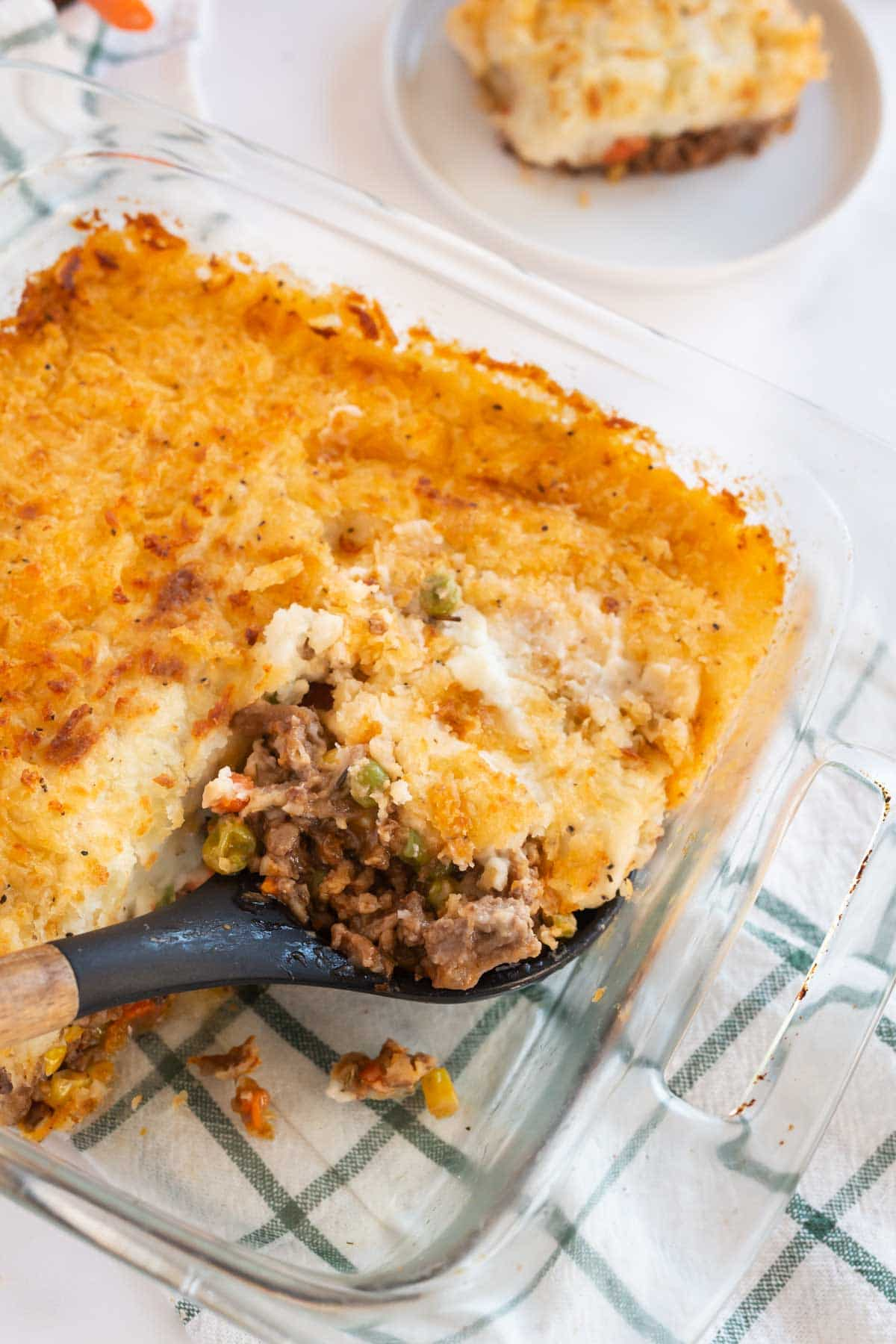 A spoon scooping a scoop of shepherd's pie out of a baking dish