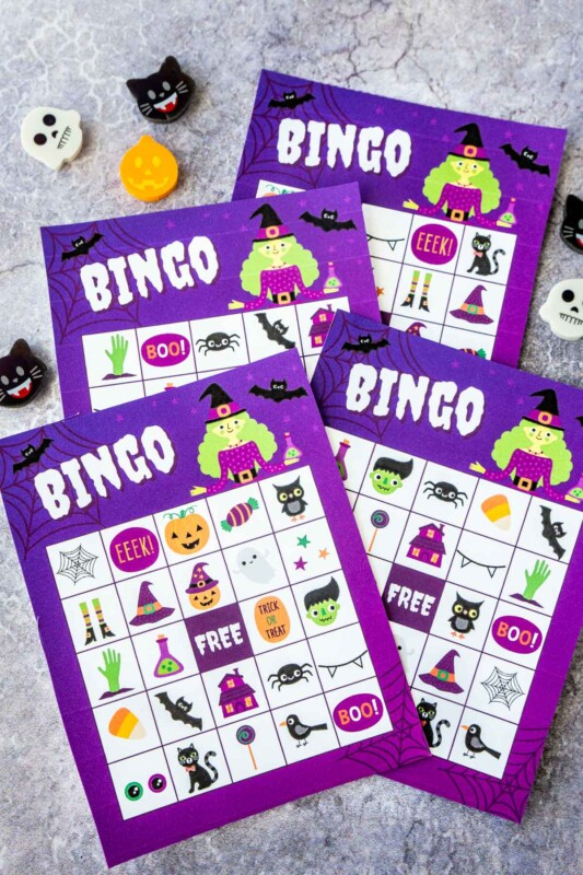 Four purple Halloween bingo cards with a witch on them