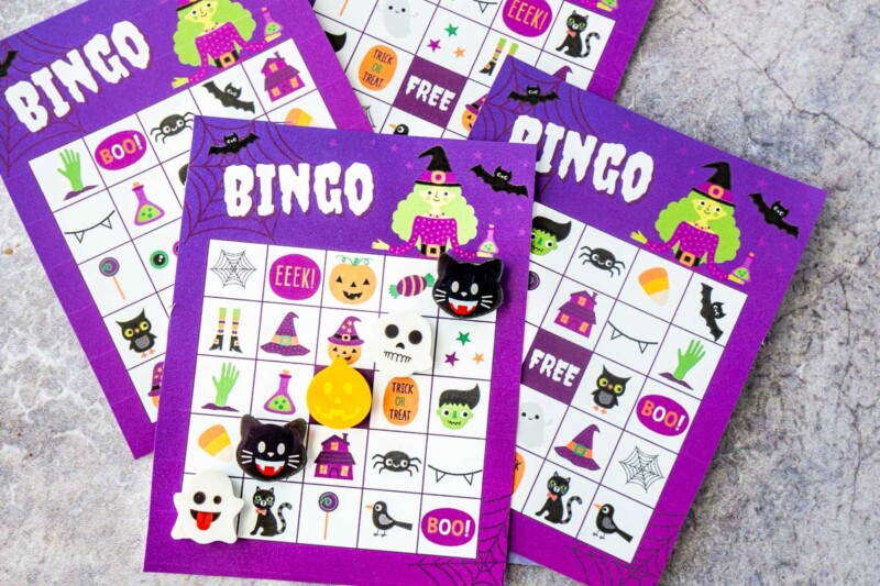 Purple Halloween bingo cards with Halloween erasers marking a bingo