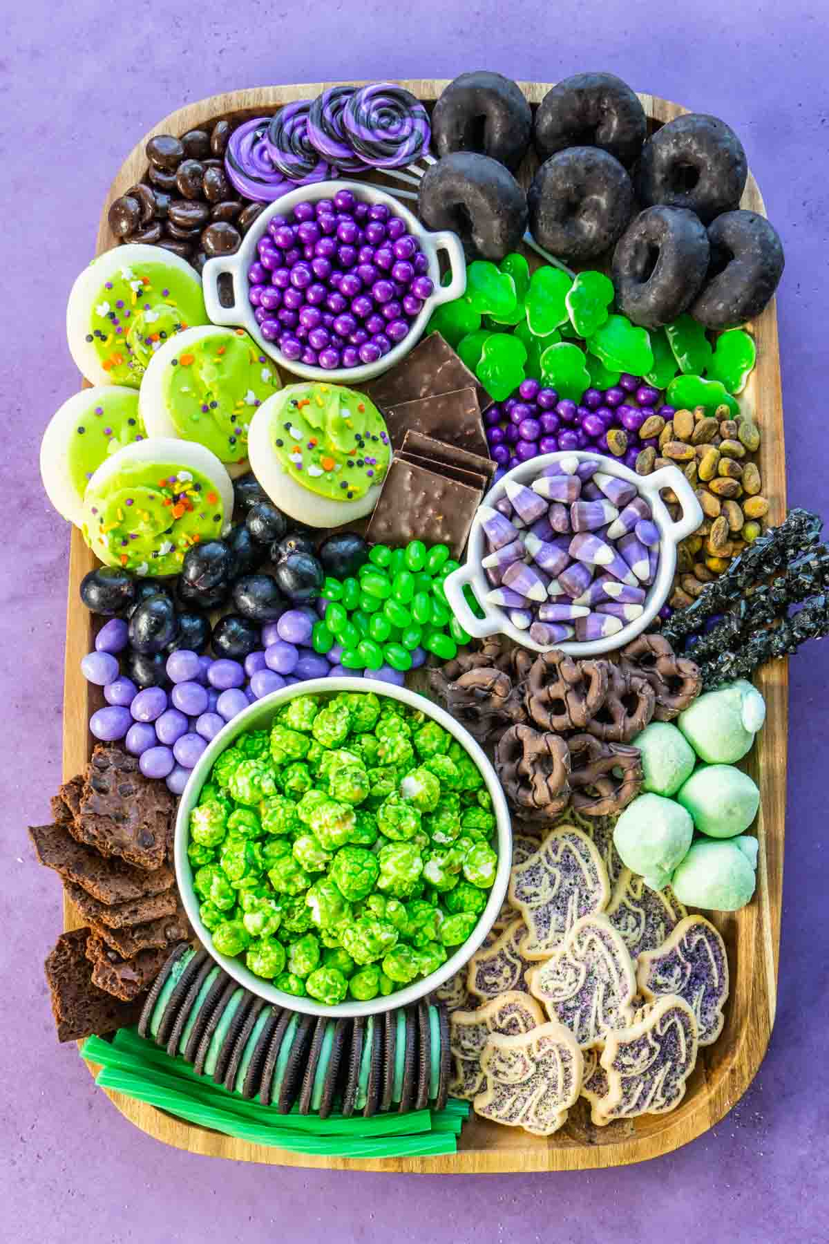 Rectangle wood tray with purple, black, and green snacks