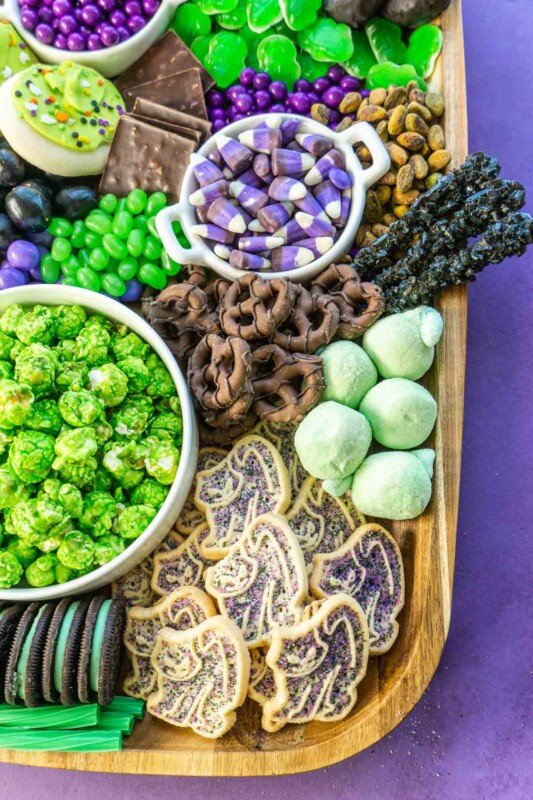 A wooden dessert board with lots of candy and cookies