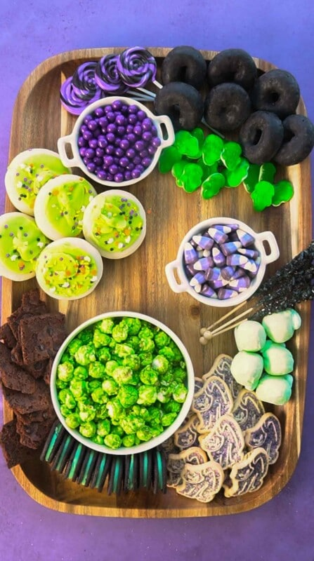 Wood board with lots of purple and green snacks