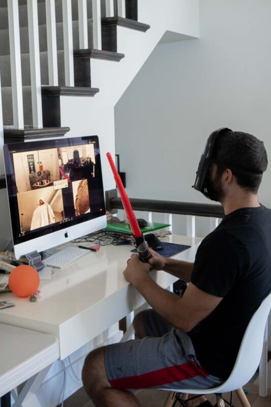 Man in a Star Wars mask sitting in front of a computer screen