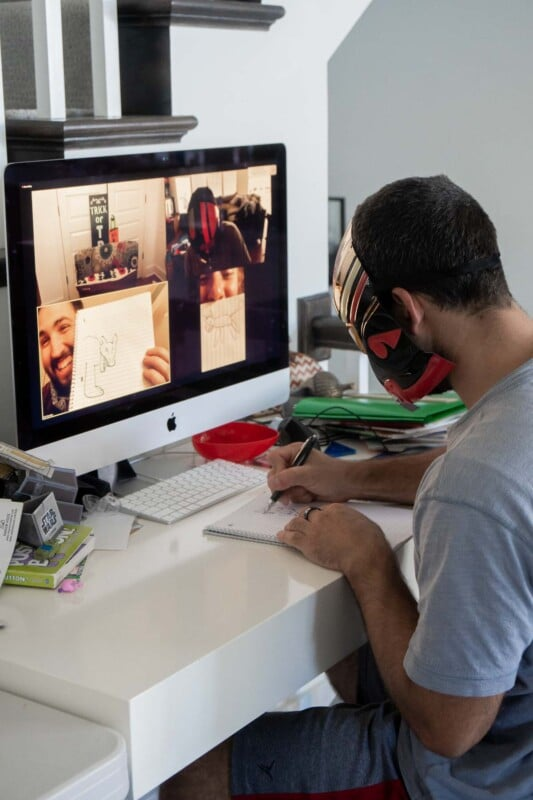 Man drawing a picture in front of a computer with people on zoom