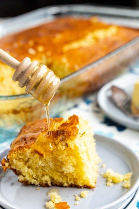 A honey dipper drizzling honey onto a piece of honey cornbread
