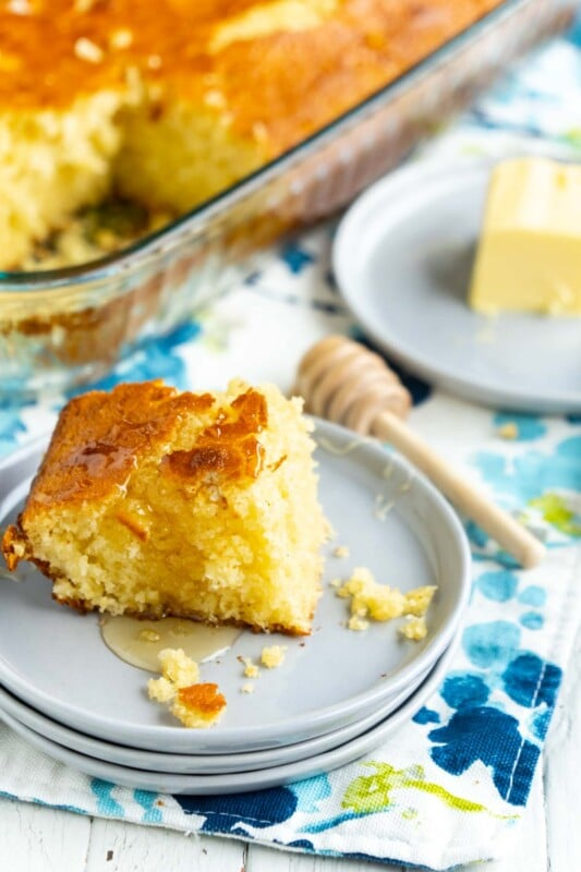 A piece of sweet cornbread on three stacked gray plates with honey and butter