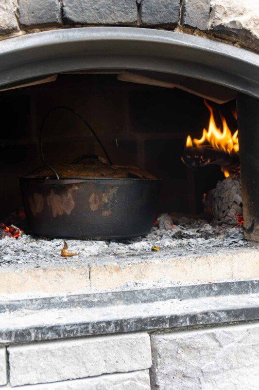 A dutch oven in a brick oven with fire behind
