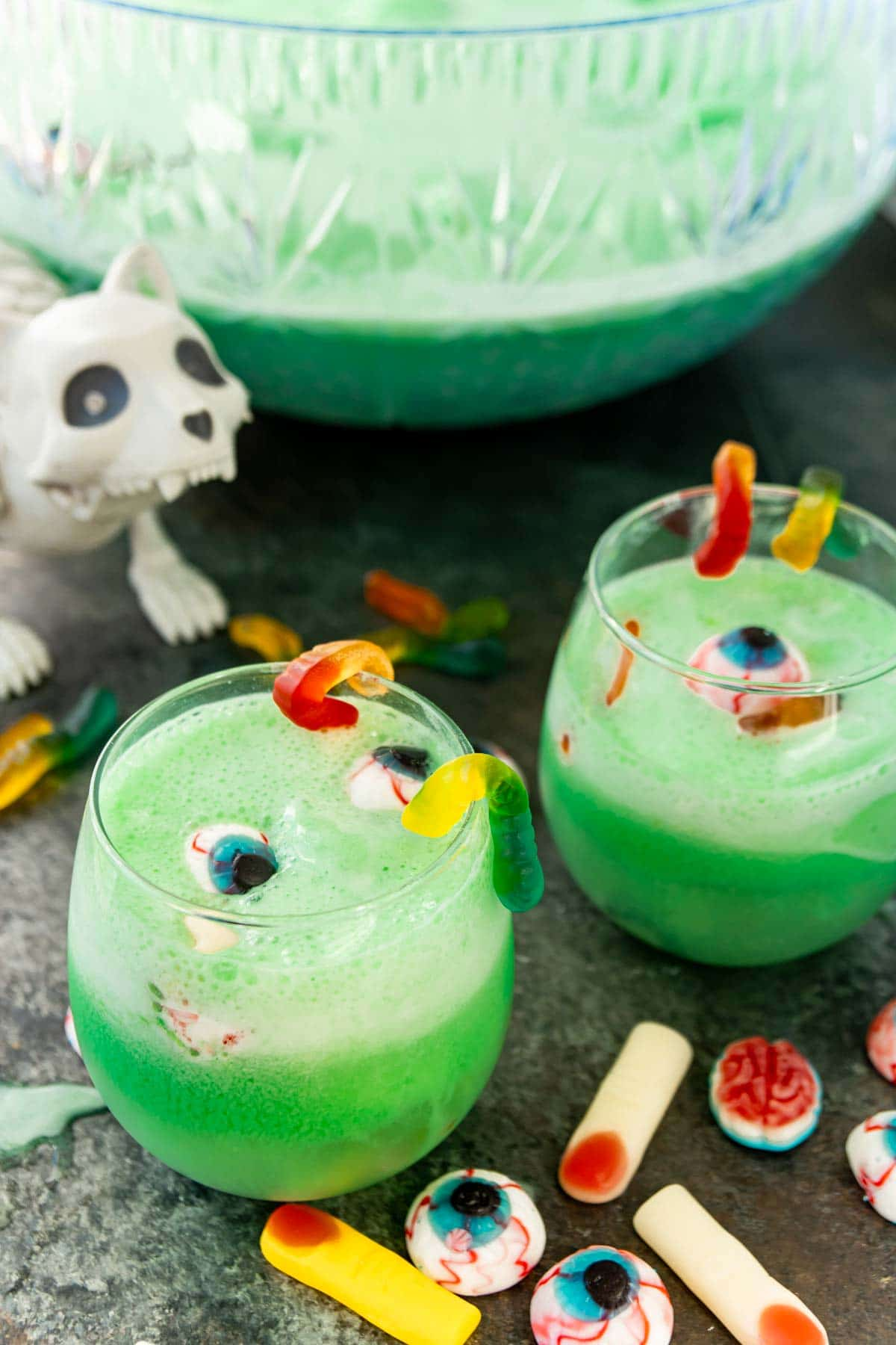Two glasses of green Halloween punch with a zombie cat