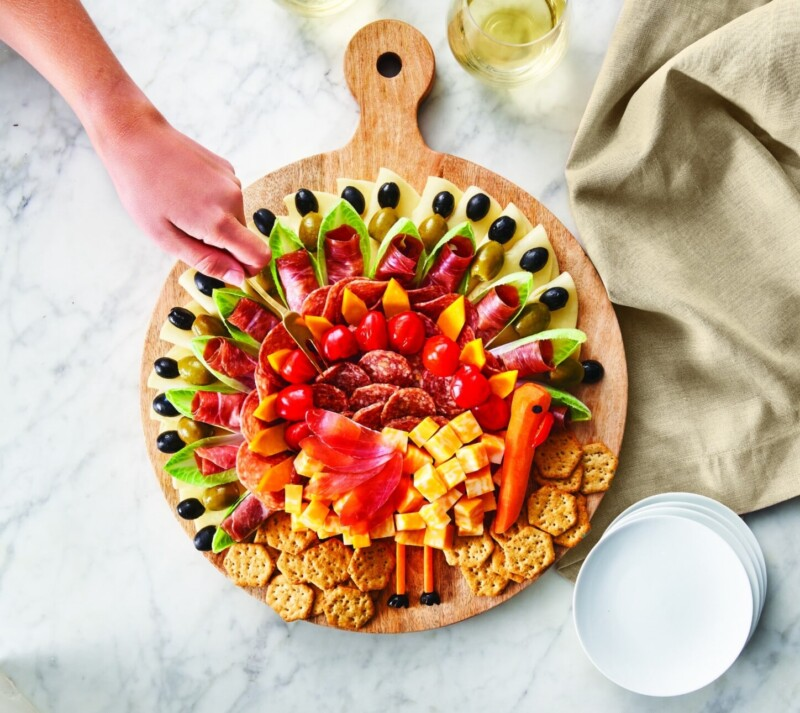 Circle charcuterie board with someone's hand