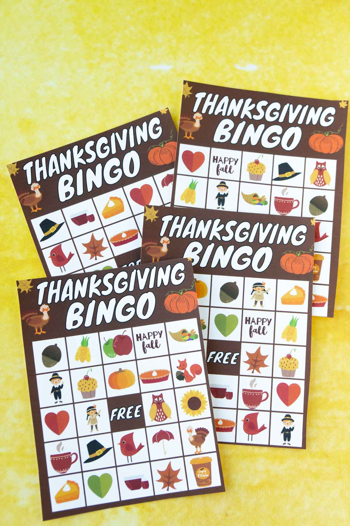 Four Thanksgiving bingo cards on a yellow background