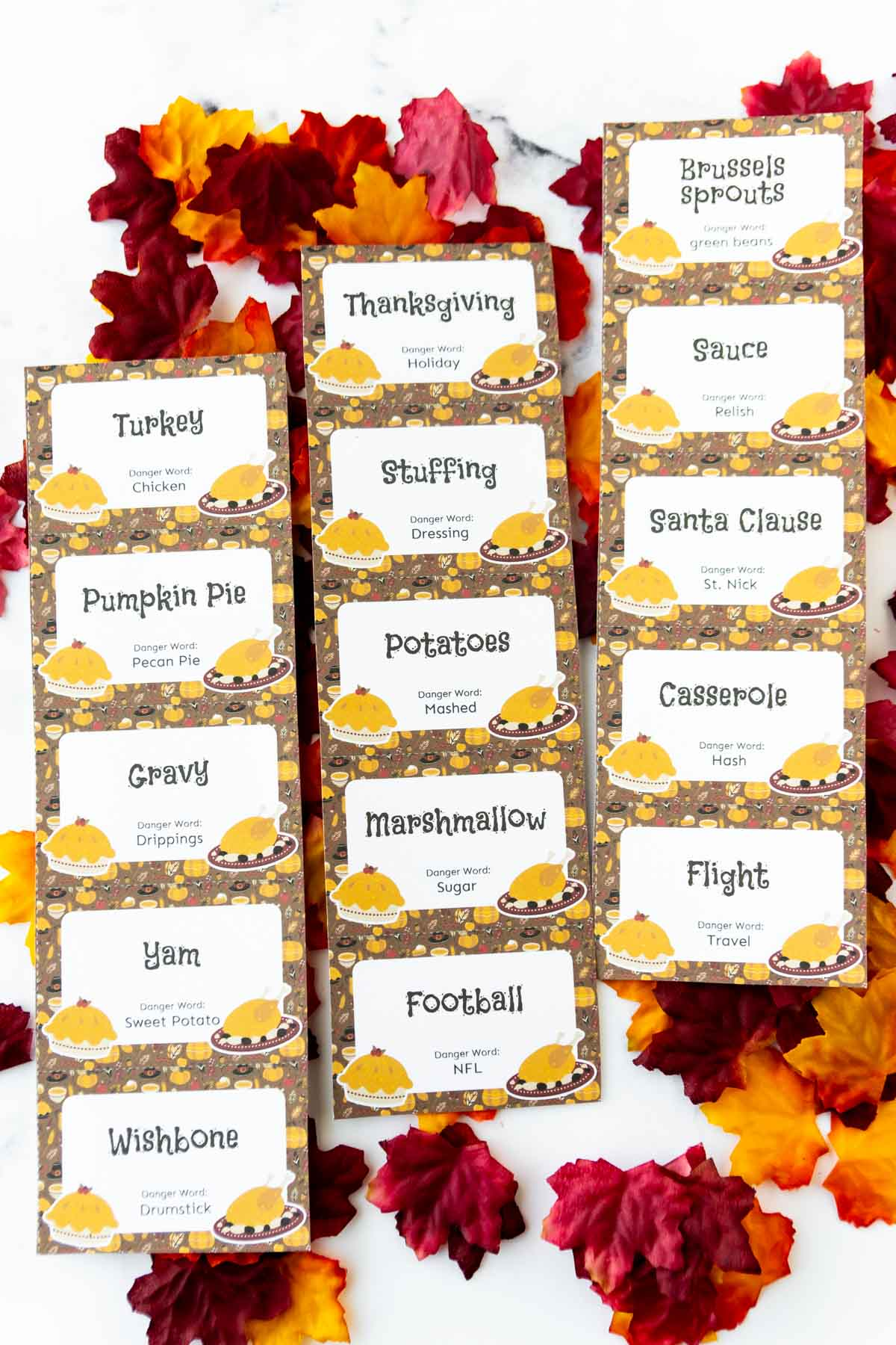 Three sheets of Thanksgiving danger words on top of plastic leaves