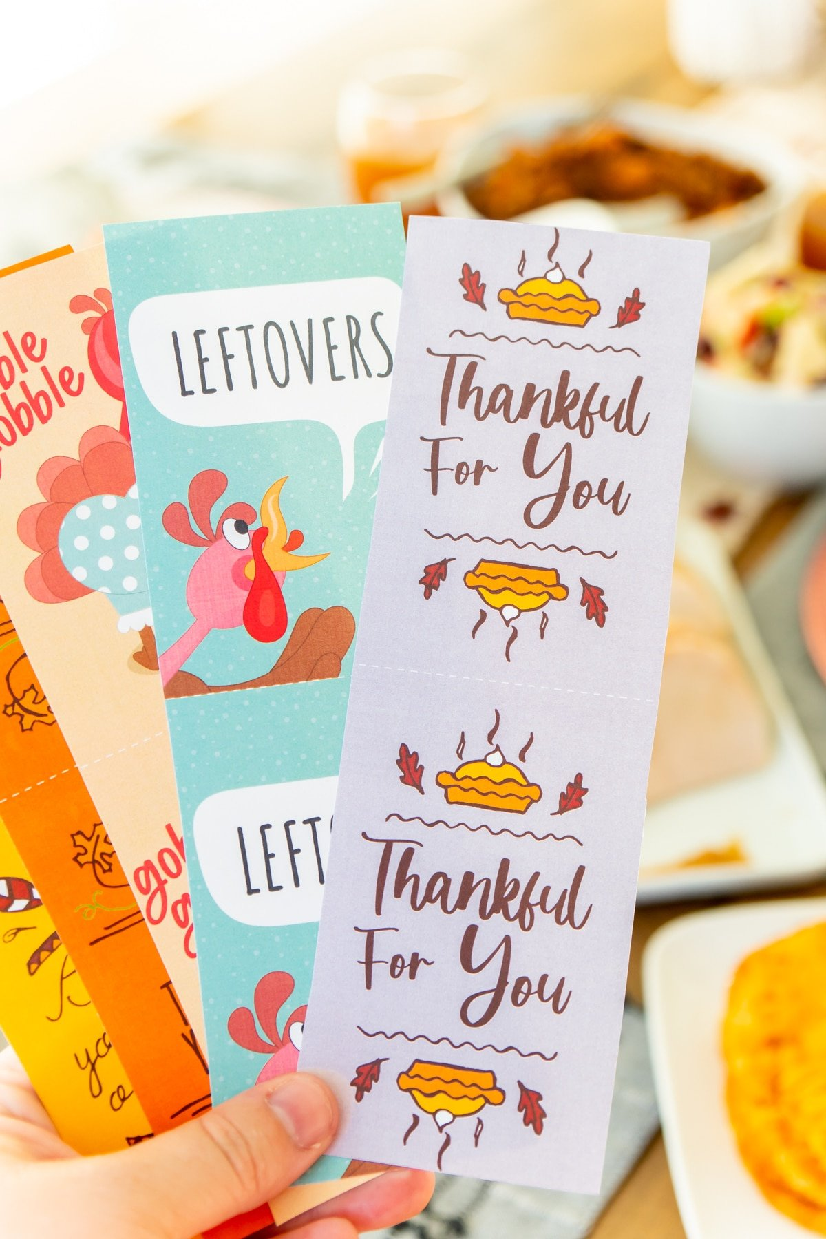 Thanksgiving gift tags being held by a woman's hand