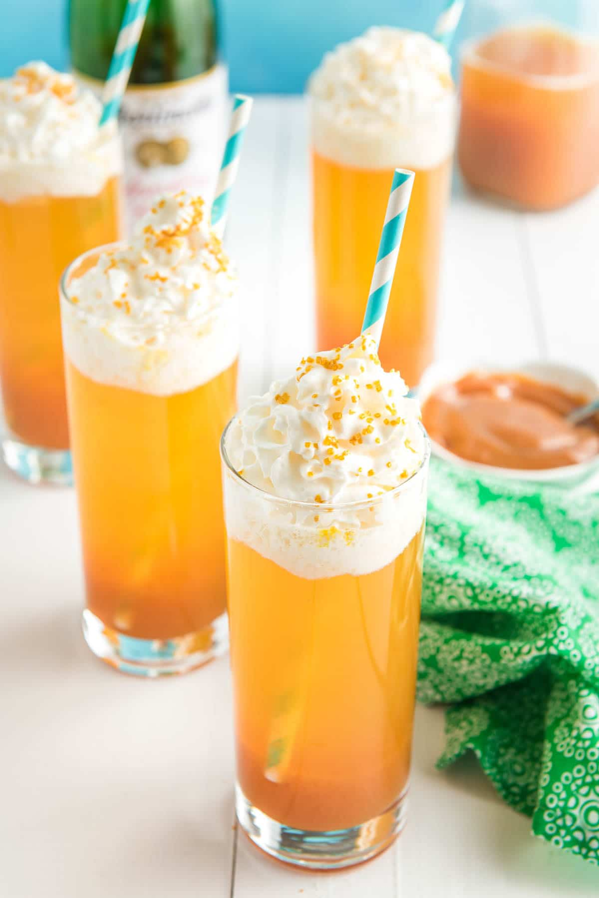 Four glasses with a caramel apple drink topped with whipped cream