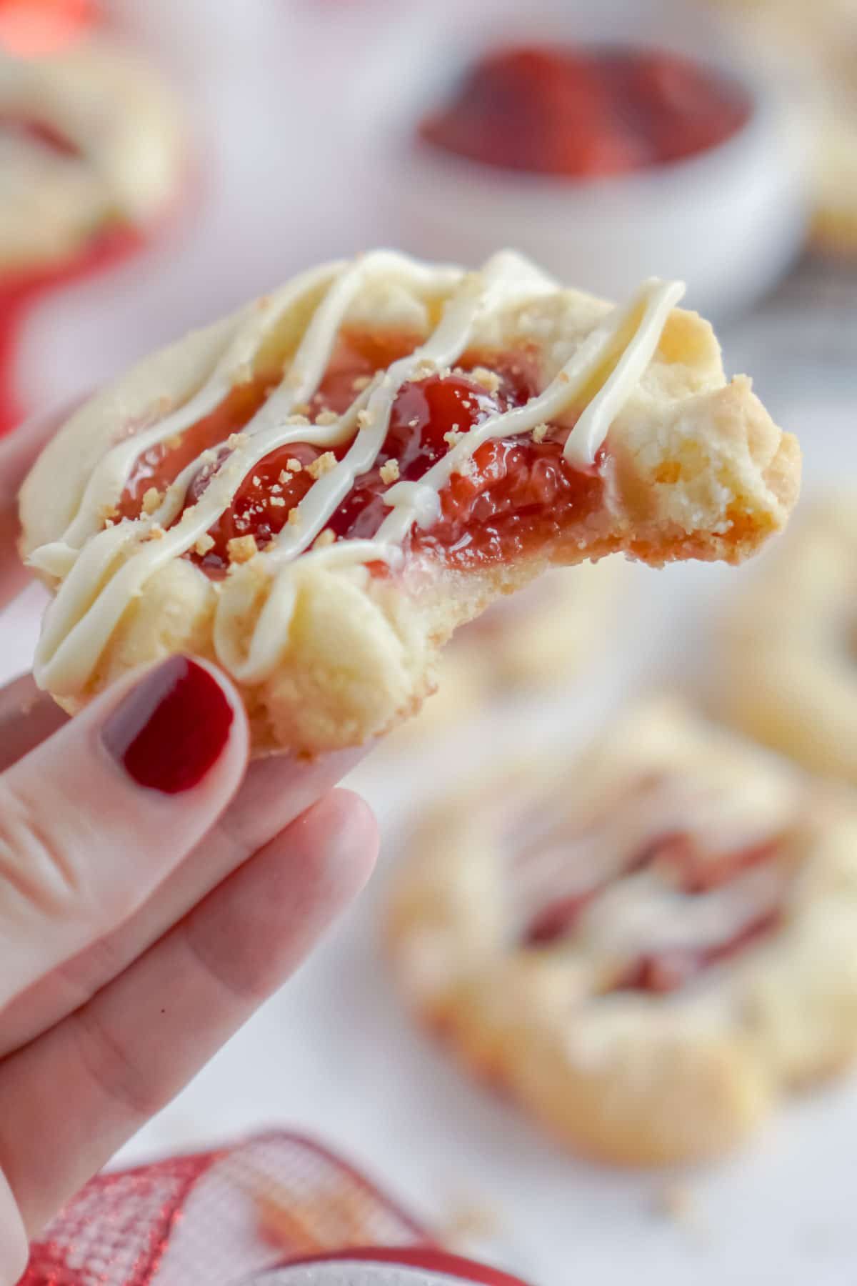 Hand holding a cherry cheesecake cookie with a bite taken out