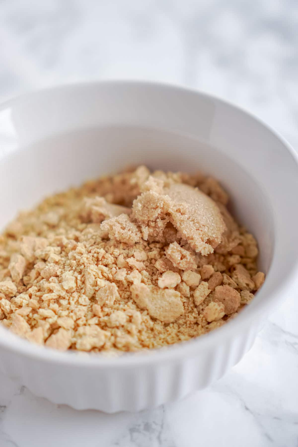 White bowl with graham cracker crumbs and brown sugar