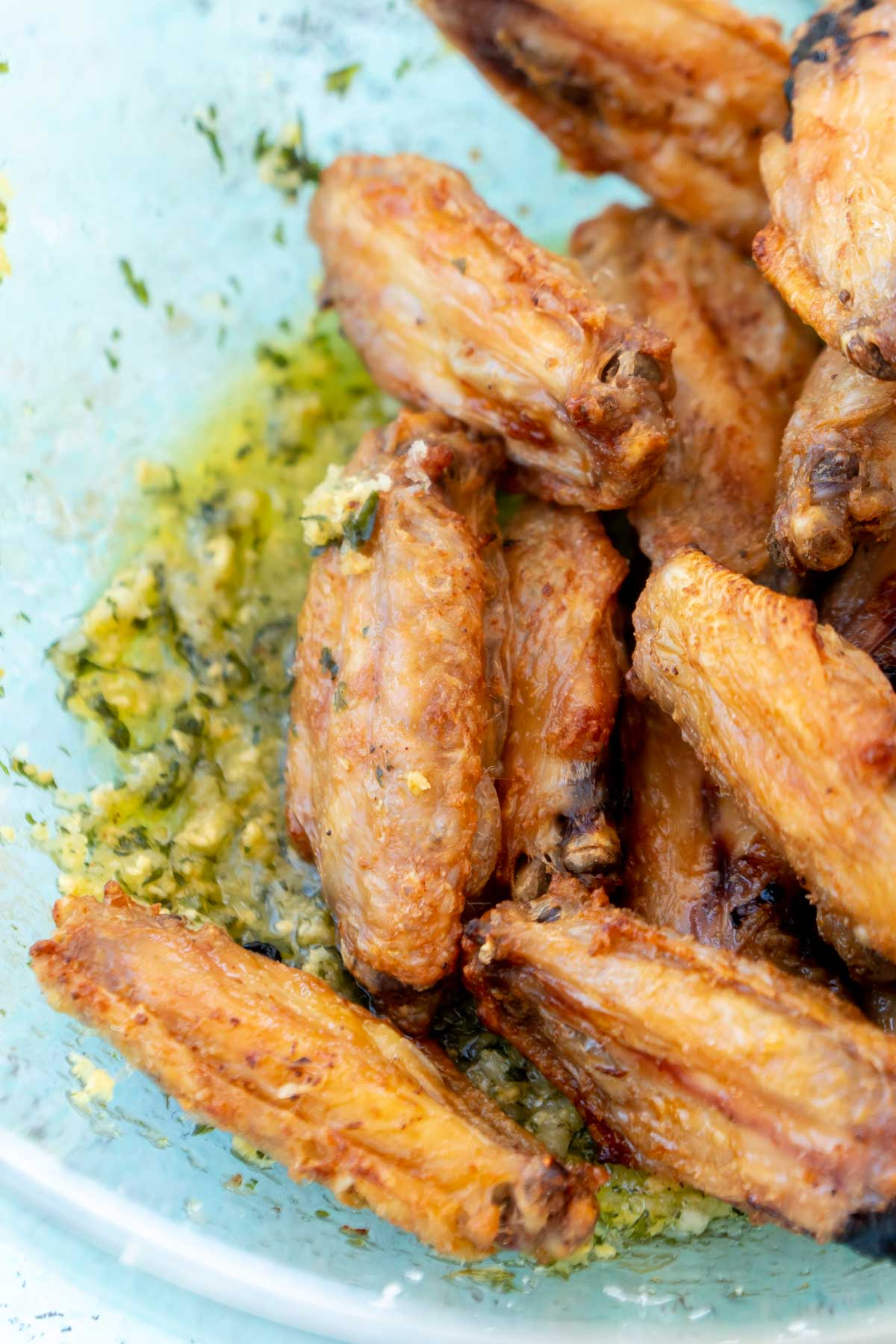 Wings in a glass bowl with garlic parmesan sauce