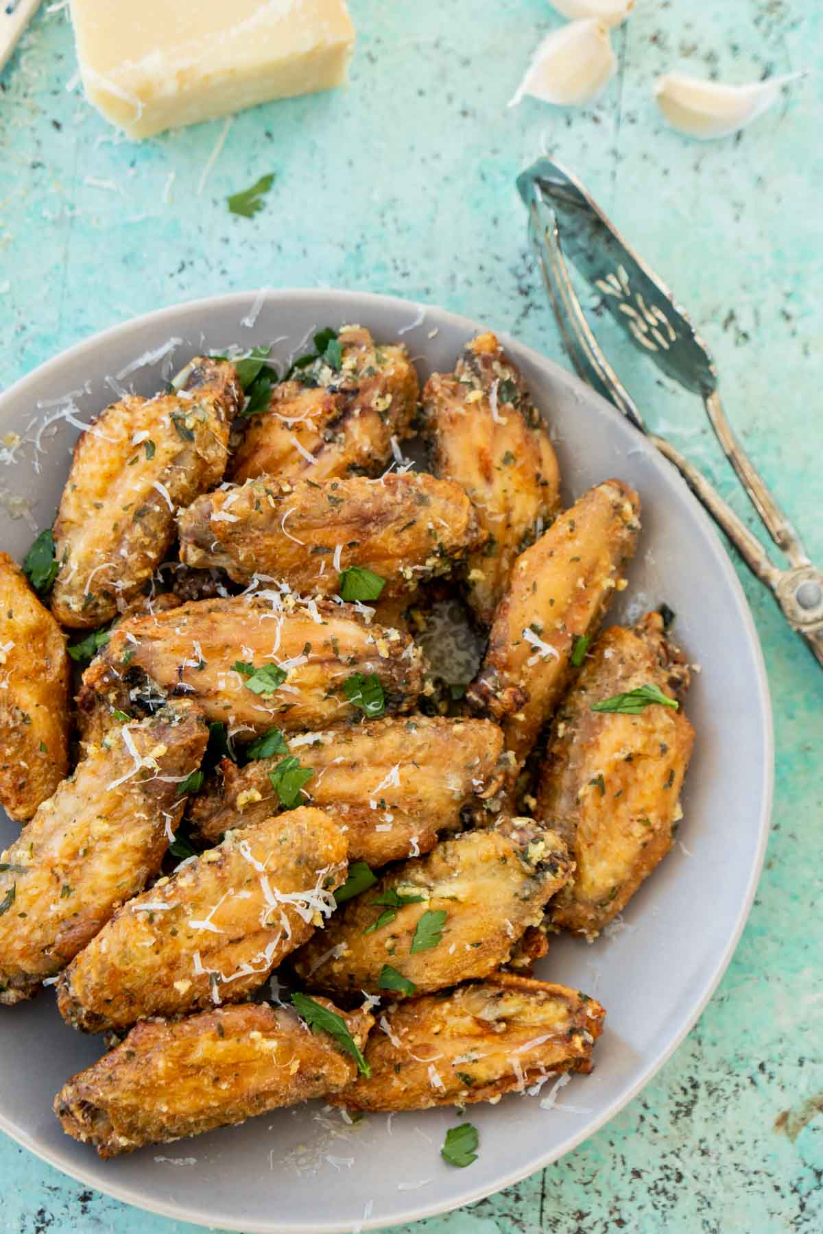 Plate of garlic parmesan wings with a block of parmesan