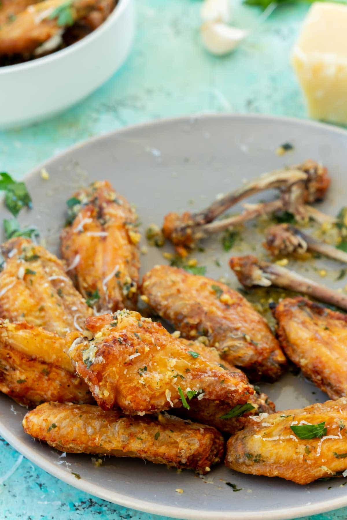 A plate of wings with a couple of wing bones