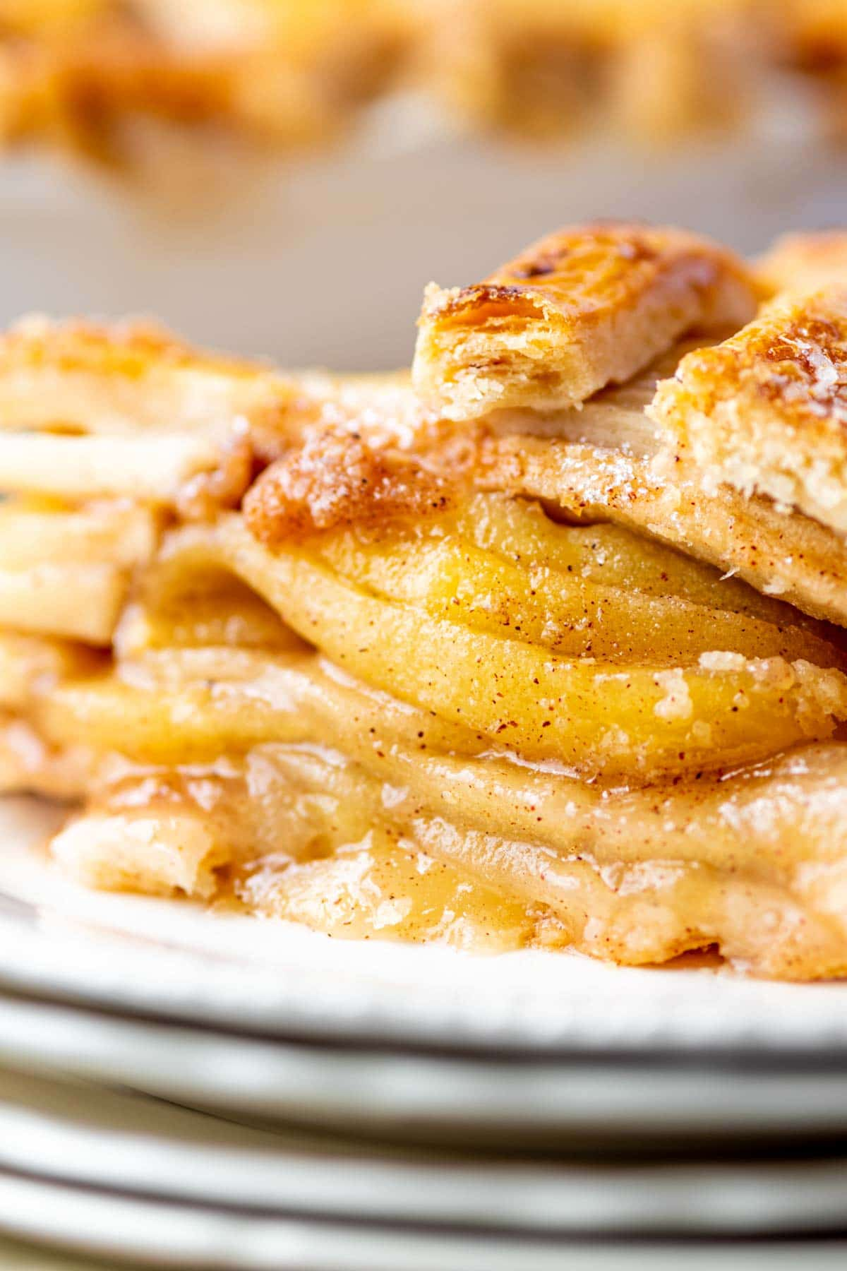 Piece of homemade apple pie on a stack of plates