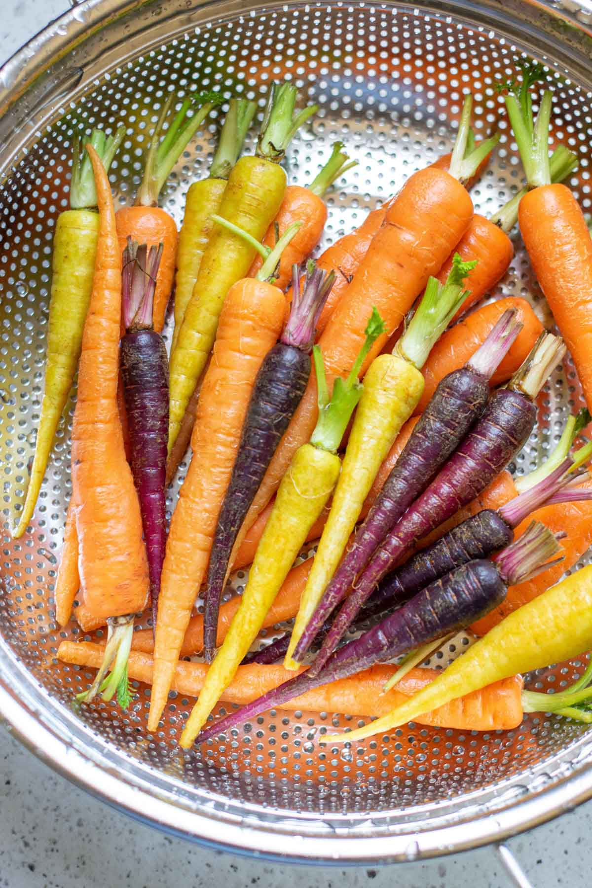 Rainbow carrots in a metal collander