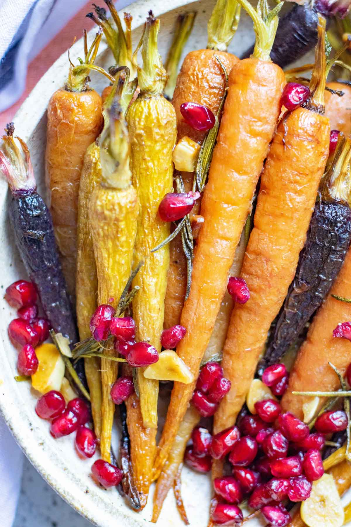 A plate of honey roasted carrots topped with pomegranate seeds