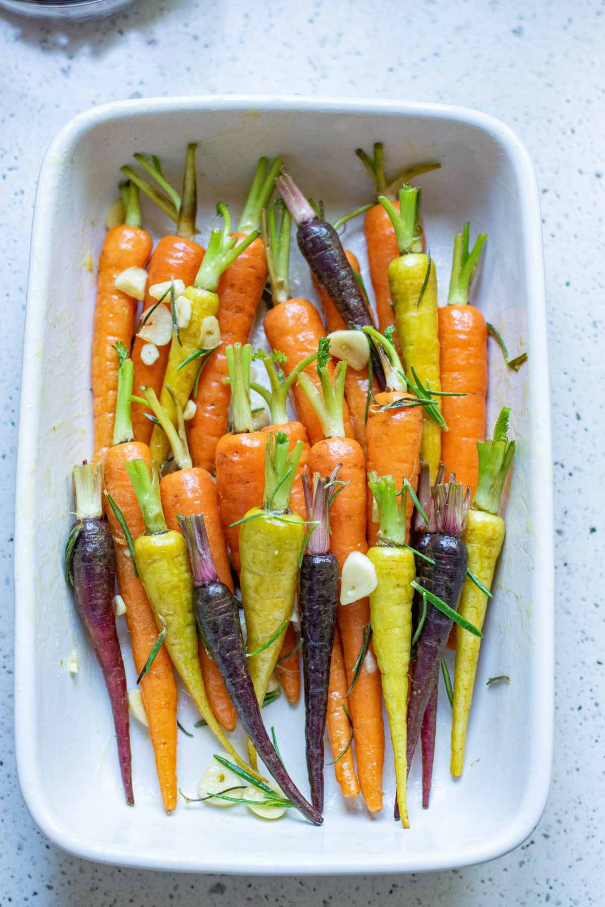 Rainbow carrots in a white rectangle baking dish
