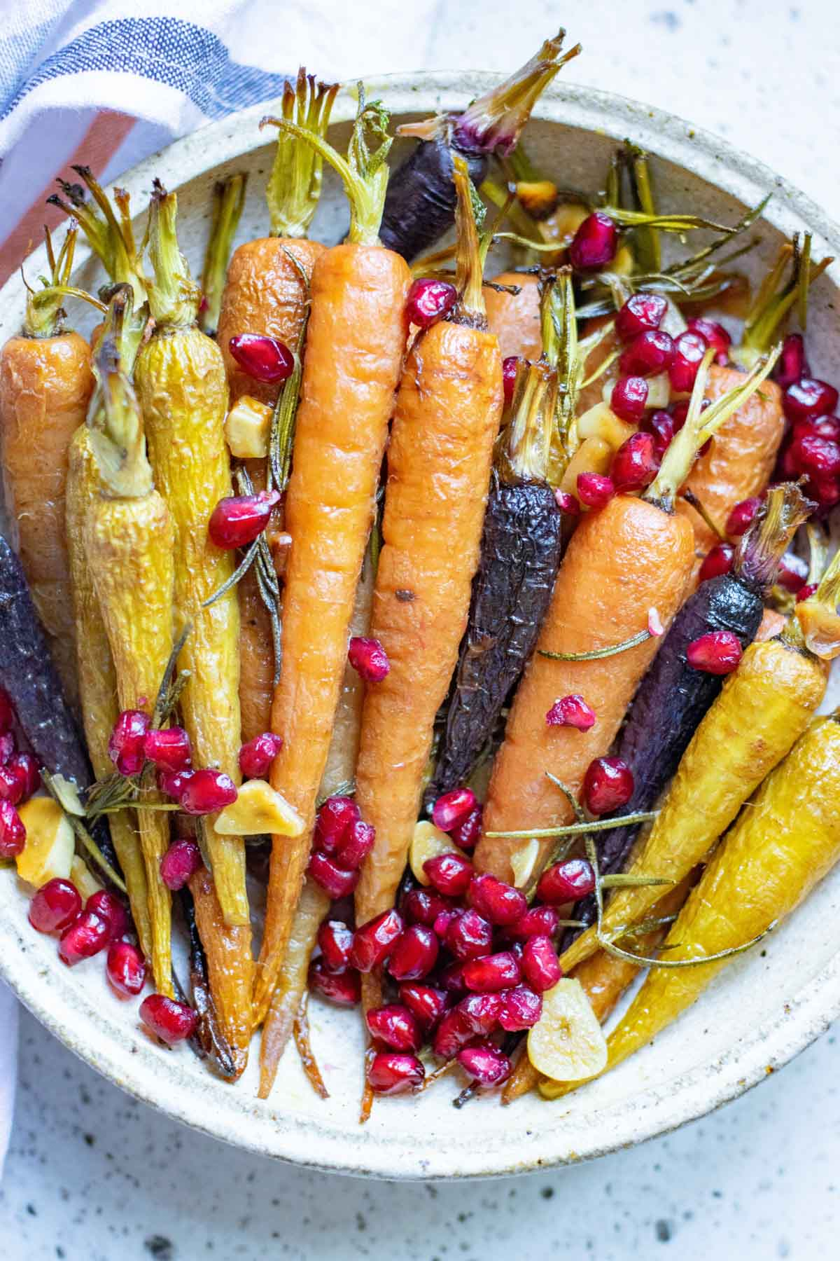 A plate of honey roasted carrots with pomegranate seeds