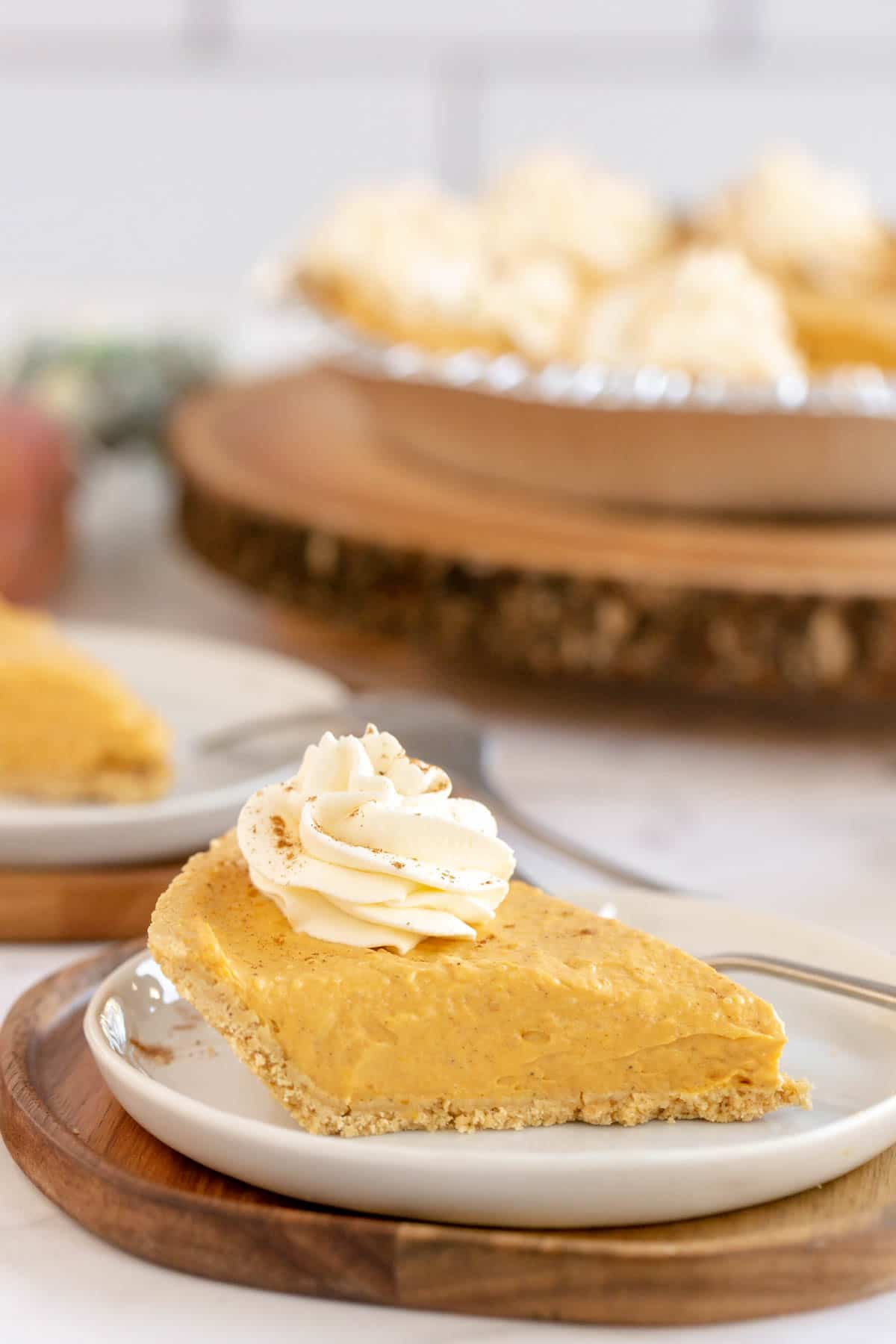A piece of no bake pumpkin pie with the rest of the pie in the background