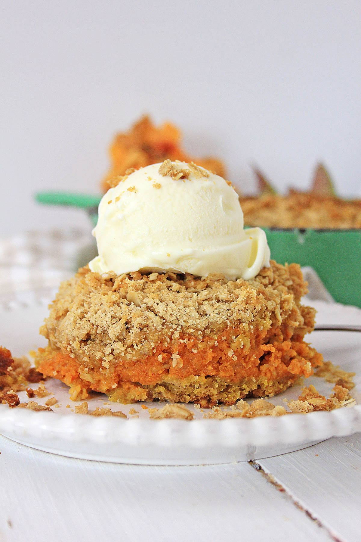 A close up image of a piece of pumpkin crisp with vanilla ice cream on top