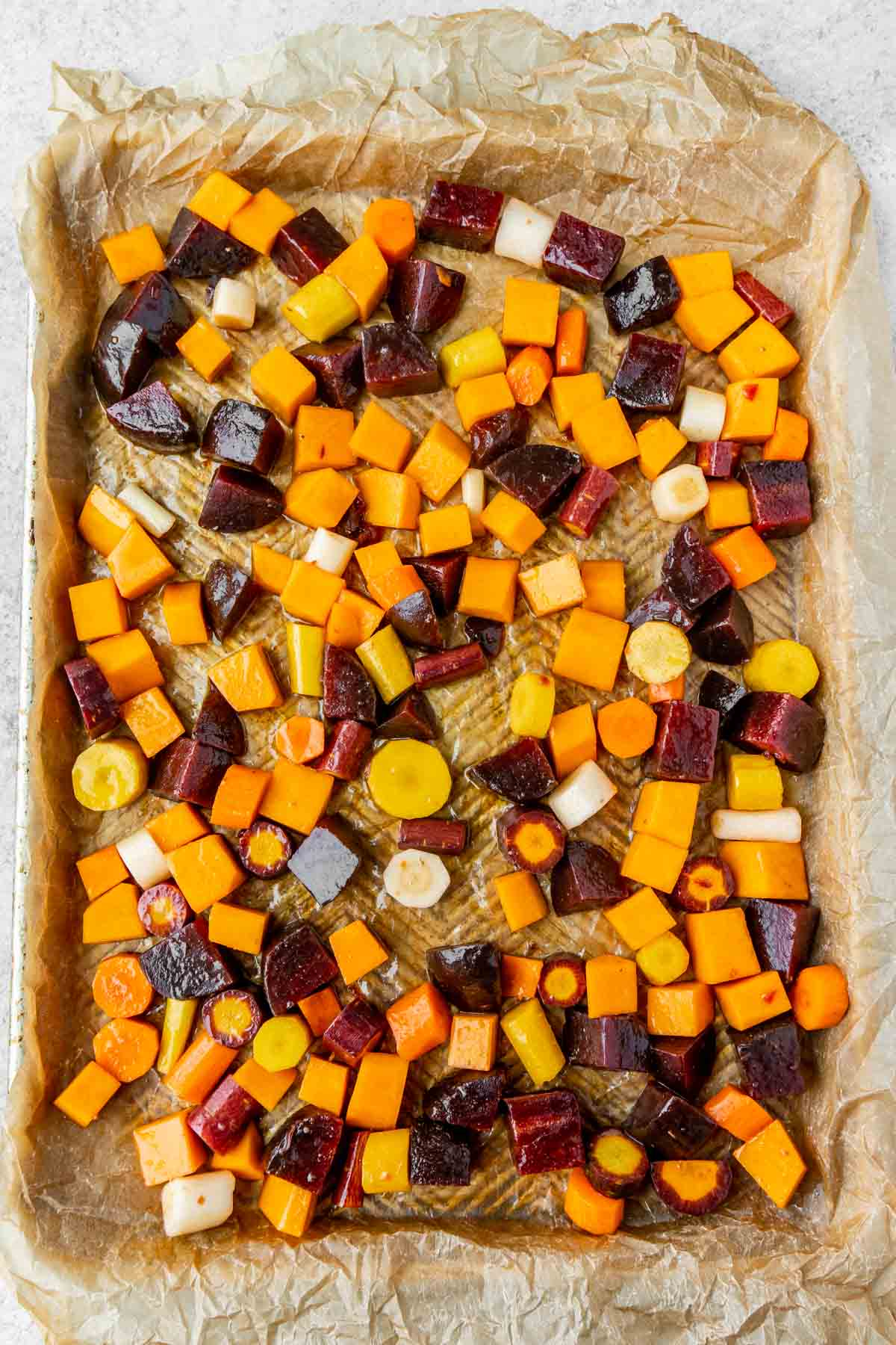 Root vegetables on a baking sheet with parchment paper