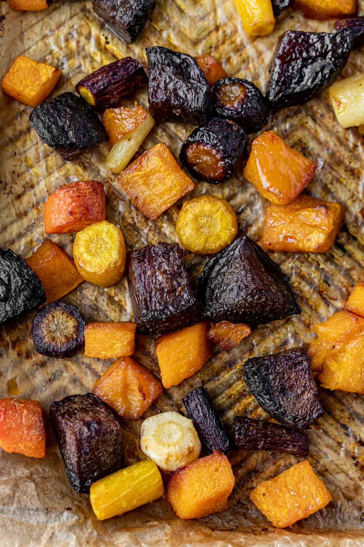 A sheet pan with roasted root vegetables on parchment paper